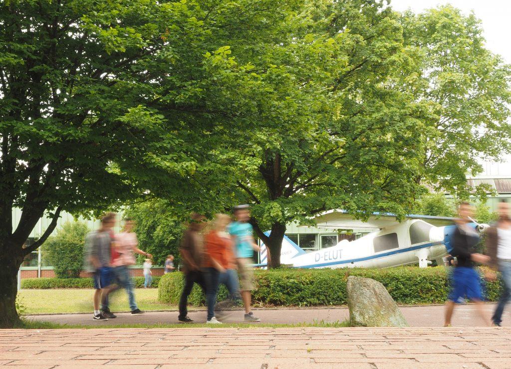 Schüler laufen zur Schule am Flieger von Claude Dornier vorbei.